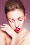 brunette woman with red full lips and red lines on her eyelids and braid hairstyle Stock Photos