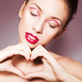 Brunette woman with red full lips and red lines on her eyelids and braid hairstyle Royalty Free Stock Image