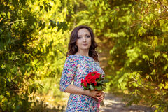 Brunette woman with red roses Royalty Free Stock Image