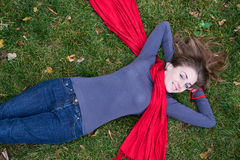 Brunette woman is in red scarf lying on the grass. Royalty Free Stock Images
