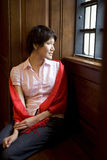 Brunette woman in a red shawl sitting by the window Stock Photography