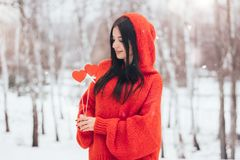 Woman holding in hand red heart for Valentine`s Day on winter background royalty free stock photography