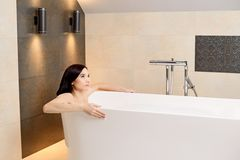 Brunette woman relaxing in bath Stock Image