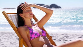 Brunette woman relaxing on a deck chair. On the beach stock footage