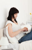 Brunette woman relaxing with her laptop on her bed Stock Image