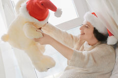 Brunette woman relaxing near window and playing with toy bear wea Stock Image