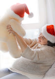 Brunette woman relaxing near window and playing with toy bear wea Royalty Free Stock Photo
