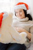 Brunette woman relaxing near window and playing with toy bear wea Royalty Free Stock Photos