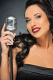 Brunette woman with a retro microphone stock photo