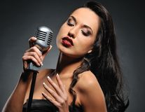 Brunette woman with a retro microphone. Attractive brunette woman with a retro microphone stock photography