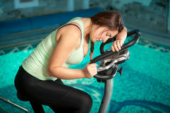 Brunette woman riding bike at fitness club Royalty Free Stock Photos