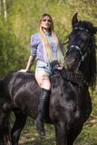 Brunette woman riding dark horse at summer green forest. Beautiful young woman on a horseback, outdoor portrait Stock Photos