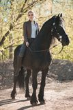 Brunette woman riding dark horse at summer green forest. Beautiful young woman on a horseback, outdoor portrait Stock Photo