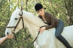 Brunette woman riding dark horse at summer green forest. Young beautiful smiling brunette woman wearing white dress riding dark horse at summer green forest Stock Images