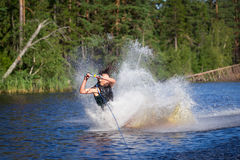 Brunette woman riding wakeboard in a summer lake Stock Images