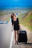 Brunette woman road suitcase. Beautiful  brunette  sexy  woman in black dress and sunglasses  go road and holds suitcase  has long hair  and elegant body Royalty Free Stock Photos