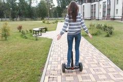 Brunette woman is rolling on gyro scooter near the home, back view. Brunette woman is rolling on gyro scooter near the home stock images