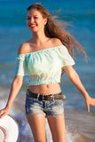Brunette woman run sea in jeans shorts Stock Photography