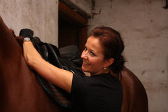 Brunette woman saddling up brown horse Royalty Free Stock Photo