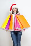 Brunette woman in santa hat holding shopping bags Royalty Free Stock Image