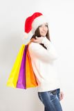 Brunette woman in santa hat holding sopping bags. Happy smiling brunette woman in santa hat holding sopping bags stock photography