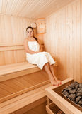Brunette woman at sauna sitting with closed eyes Stock Images
