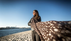 Brunette woman in scarf posing on beach at windy day Stock Photography