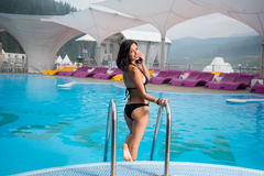 Brunette woman in a black bikini near swimming pool and turning back to smile at the camera on mountain resort Royalty Free Stock Photos