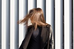 Brunette model with shiny long hair blowing in wind, walking at. Brunette woman with shiny long hair blowing in wind, walking at the street royalty free stock photos