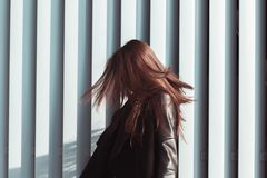 Brunette model with shiny long hair fluttering in wind, walking. Brunette woman with shiny long hair fluttering in wind, walking at the street stock photography