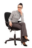 Brunette woman in shirt and trousers sitting in office chair Stock Image