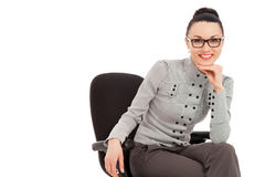 Brunette woman in shirt and trousers sitting in office chair Royalty Free Stock Images