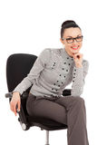 Brunette woman in shirt and trousers sitting in office chair Royalty Free Stock Photography