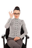 Brunette woman in shirt and trousers sitting in office chair Stock Photography