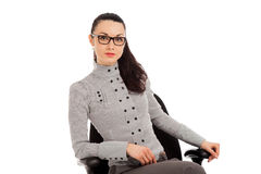 Brunette woman in shirt and trousers sitting in office chair Stock Images