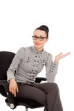 Brunette woman in shirt and trousers sitting in office chair pre Royalty Free Stock Photo