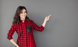Brunette woman showing with her finger to copy space Stock Images
