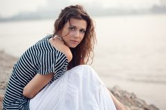 Brunette woman sitting on beach. Beautiful brunette   woman portrait sitting on stone beach Stock Photos