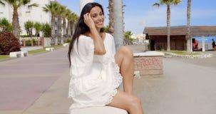 Brunette Woman Sitting on Beach Promenade Wall stock video