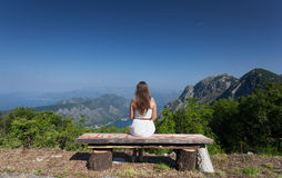 Brunette woman sitting on bench at high mountain Royalty Free Stock Images