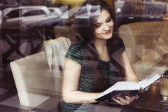 Brunette woman sitting at the cafe reading book, studing and drinking coffee Stock Photos