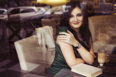 Brunette woman sitting at the cafe reading book, studing and drinking coffee Stock Photography