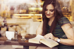 Brunette woman sitting at the cafe reading book, studing and drinking coffee Stock Photo