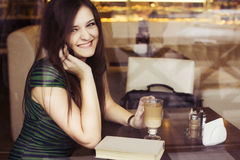 Brunette woman sitting at the cafe reading book, studing and drinking coffee and talking on the phone Royalty Free Stock Photos