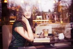 Brunette woman sitting at the cafe reading book, studing and drinking coffee and talking on the phone Stock Image