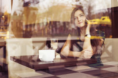 Brunette woman sitting at the cafe reading book, studing and drinking coffee and talking on the phone Stock Photography