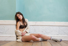 Brunette woman sitting on floor alone in underwear and sweater Stock Image