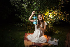 Brunette woman sitting at garden at night and holding old lanter Royalty Free Stock Images