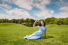 Brunette woman sitting on green grass with retro camera Stock Photo