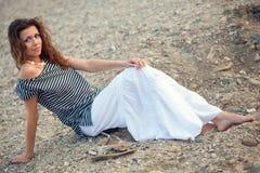 Brunette woman sitting on ground. Beautiful brunette   woman portrait sitting on coast Stock Photo
